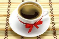 Taza de café con el arqueamiento rojo Fotografía de archivo
