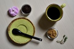Taza de café con el azúcar de caña y la rosa negra del rosa de la cuchara Imagen de archivo libre de regalías