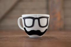 Taza de café con el bigote y las lentes en la tabla Imagen de archivo libre de regalías