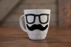 Taza de café con el bigote y las lentes en la tabla Fotos de archivo
