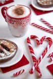 Taza de café con el caramelo de la Navidad de la forma del corazón y las mini tortas Fotografía de archivo libre de regalías