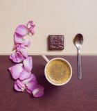 Taza de café con el caramelo, los pétalos y la cuchara foto de archivo