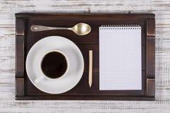 Taza de café con el cuaderno en una bandeja en la tabla de madera blanca Concepto de la forma de vida Ciérrese para arriba, visió Fotos de archivo libres de regalías