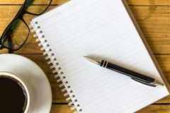Taza de café con el cuaderno en una tabla de madera para el diseño y el backgr Imagenes de archivo