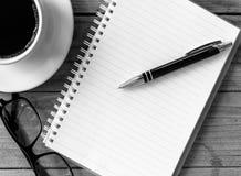 Taza de café con el cuaderno en una tabla de madera para el diseño y el backgr Imagen de archivo