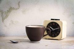 Taza de café con el despertador Imagenes de archivo