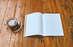 Taza de café con el espacio en blanco del libro Fotos de archivo