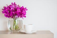 Taza de café con el florero de la orquídea fotos de archivo