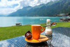 Taza de café con el fondo de la montaña y del lago Foto de archivo