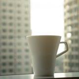 Taza de café con el fondo del scape de la ciudad Imágenes de archivo libres de regalías