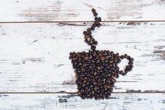 Taza de café con el levantamiento del vapor hecho de los granos de café asados Imagenes de archivo
