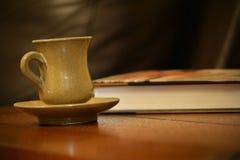 Taza de café con el libro en la tabla Fotos de archivo