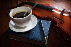 Taza de café con el libro, la pluma y el violín Imagen de archivo