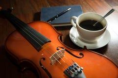 Taza de café con el libro, la pluma y el violín Imagenes de archivo