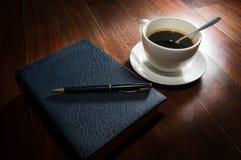 Taza de café con el libro y la pluma Fotografía de archivo