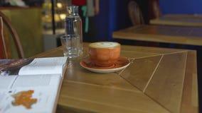 Taza de caf? con el modelo en la tabla en caf? Arte Tabla en el caf? acogedor en el cual hay taza de caf? y de libro Coffe, caf almacen de video