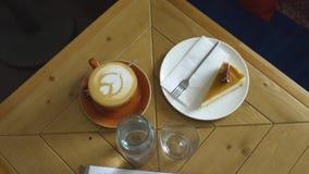 Taza de caf? con el modelo en la tabla en caf? Arte Tabla en el caf? acogedor en el cual hay taza de caf? y de postre Coffe metrajes