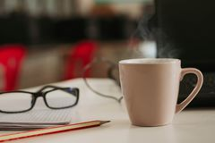 Taza de café con el palillo de canela en la tabla de madera imagen de archivo