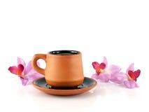 Taza de café con el platillo y las flores artificiales de la orquídea aislados en el fondo blanco Fotos de archivo