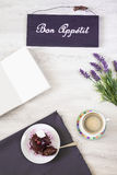 Taza de café con el postre y el cuaderno en la tabla Fotografía de archivo