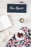 Taza de café con el postre y el cuaderno en la tabla Fotos de archivo libres de regalías
