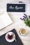 Taza de café con el postre y el cuaderno en la tabla Fotos de archivo