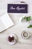 Taza de café con el postre y el cuaderno en la tabla Fotografía de archivo libre de regalías