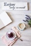 Taza de café con el postre y el cuaderno en la tabla Imagenes de archivo