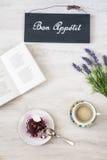 Taza de café con el postre y el libro en la tabla Fotos de archivo libres de regalías