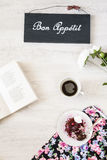 Taza de café con el postre y el libro en la tabla Imagen de archivo libre de regalías