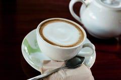 Taza de café con el pote caliente del té en de madera adentro sobre tono oscuro Imagenes de archivo