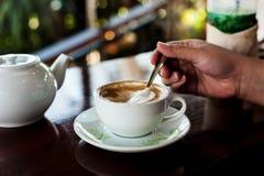 Taza de café con el pote caliente del té en de madera adentro sobre tono oscuro Foto de archivo