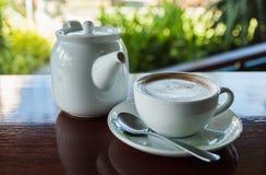 Taza de café con el pote caliente del té en fondo de madera y de la falta de definición Fotos de archivo