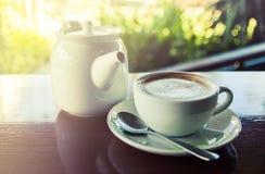 Taza de café con el pote caliente del té en fondo de madera y de la falta de definición Imagenes de archivo