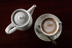 Taza de café con el pote caliente del té en una oscuridad de madera Foto de archivo libre de regalías