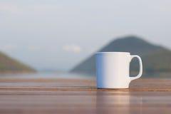 Taza de café con el río y la montaña Fotografía de archivo