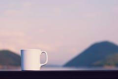 Taza de café con el río y la montaña Imagenes de archivo