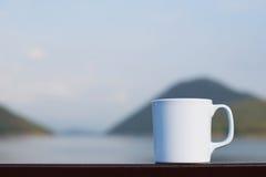 Taza de café con el río y la montaña Foto de archivo libre de regalías