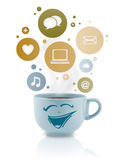 Taza de café con el social e iconos de los medios en burbujas coloridas Imagen de archivo libre de regalías