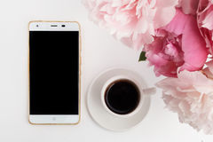 Taza de café con el teléfono y las peonías en el fondo blanco Endecha plana Visión superior Foto de archivo