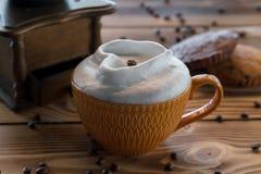 Taza de café con espuma bajo la forma de corazón con las galletas y los granos de café con la amoladora de café en una tabla de m Imágenes de archivo libres de regalías