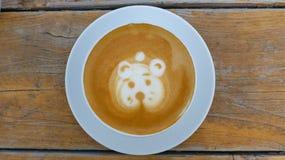 Taza de café con espuma de la leche en una tabla de madera Fotos de archivo libres de regalías