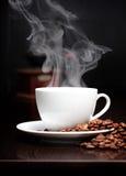 Taza de café con humo y grano Imagen de archivo