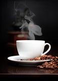 Taza de café con humo y grano Fotos de archivo