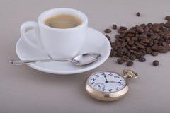 Taza de café con la cuchara, el reloj de bolsillo y los granos de café imagen de archivo