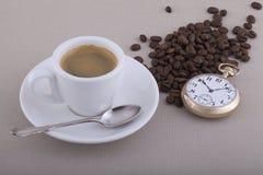 Taza de café con la cuchara, el reloj de bolsillo y los granos de café imagenes de archivo