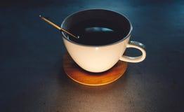 taza de café con la cuchara de oro y el platillo de madera en la tabla concreta imagenes de archivo