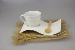 Taza de café con la cucharilla en fondo del aislante de la materia textil del yute Foto de archivo libre de regalías