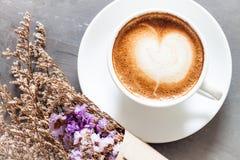 Taza de café con la flor violeta hermosa Foto de archivo