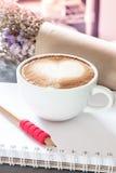Taza de café con la libreta en fondo gris Imagen de archivo libre de regalías
